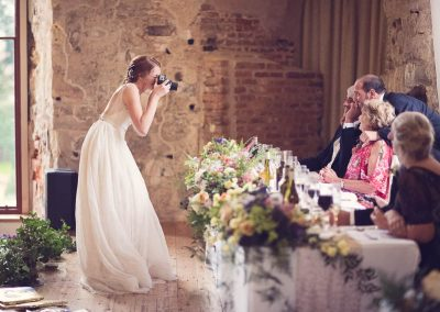 Boho chique bride takes Polaroid photograph of wedding party at top table covered in flowers at Dorset castle wedding venue