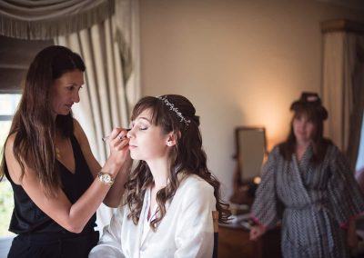 Bride wedding having wedding make up styled photograph with mother watching at Hethfelton House by one thousand words in Dorset