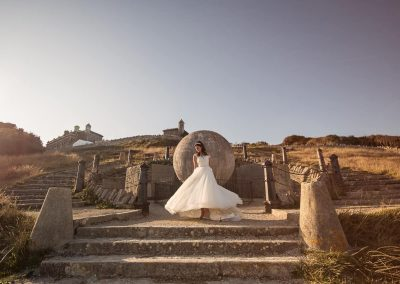 Bride in white wedding dress twirls in front of stone globe at Dorset sea side castle wedding venue by one thousand words photography