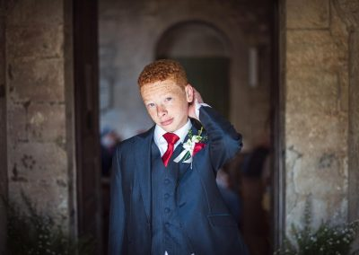 Young usher in blue wedding suit at Dorset church stone doorway photograph by one thousand words documentary photography