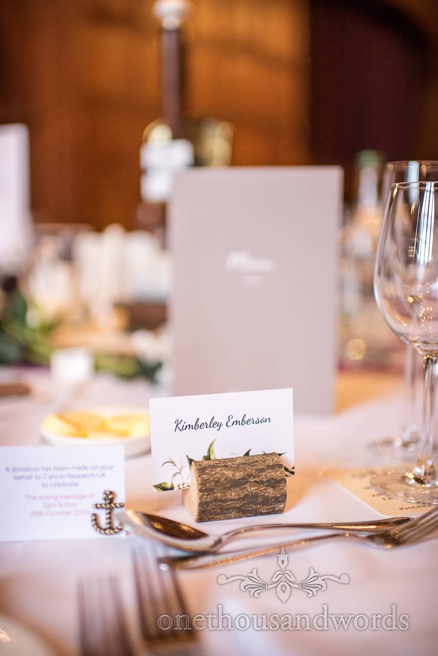 Detail wedding photograph of brides table name place set in slice of wood in among cutlery and wine glasses