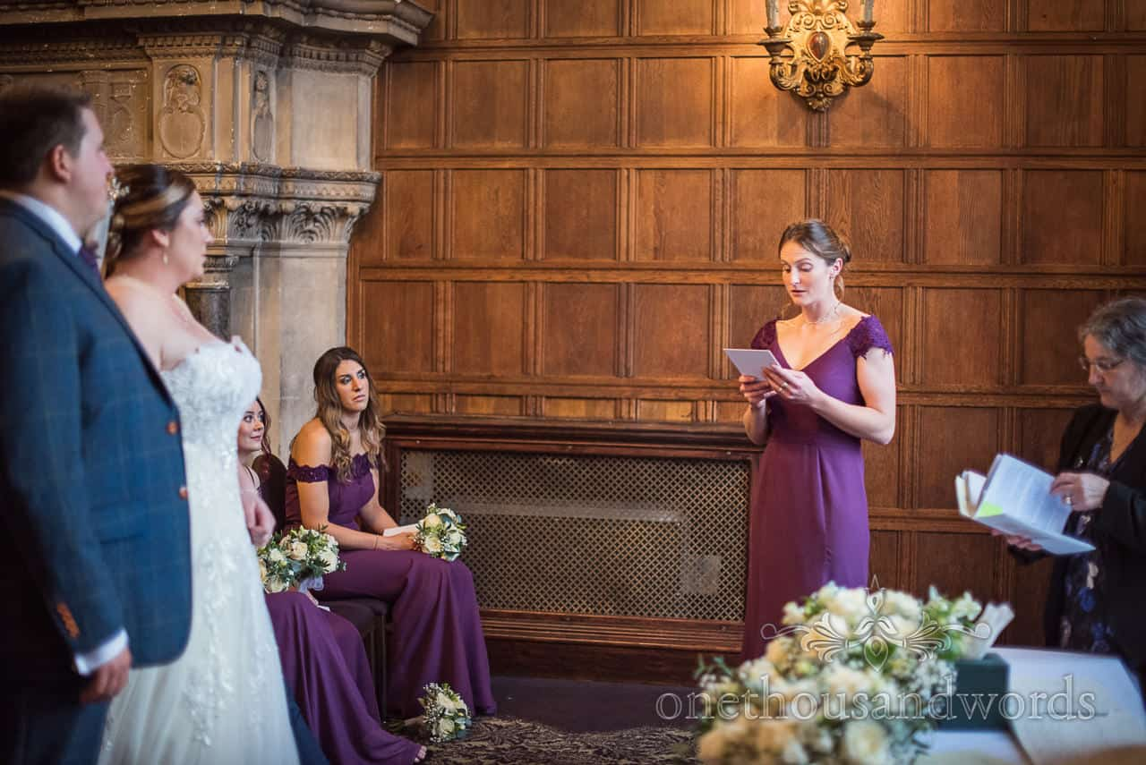 Bridesmaid in purple dress delivers wedding ceremony reading to bride and groom against dark oak paneled wall