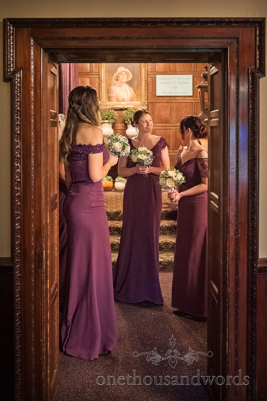 Bridesmaids in purple dresses gather in dark wood doorway before wedding ceremony at Rhinefield House Hotel