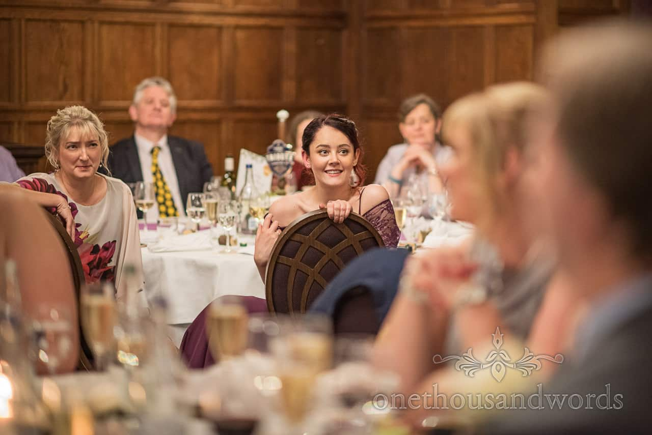 Bridesmaid smiles during wedding speeches in oak paneled room at Rhinefiled House Hotel in the New Forest