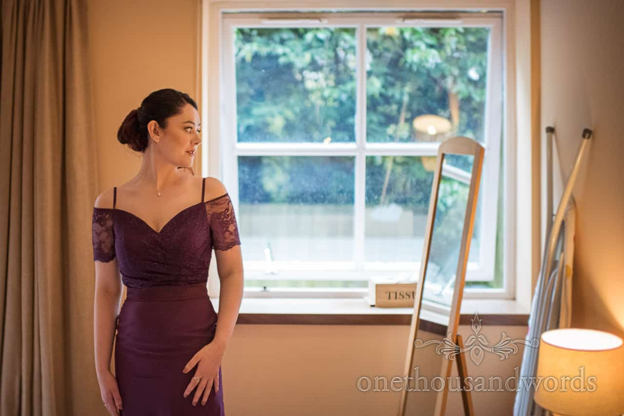 Bridesmaid in purple dress checks her reflection in mirror in front of bed and breakfast window during bridal preparations