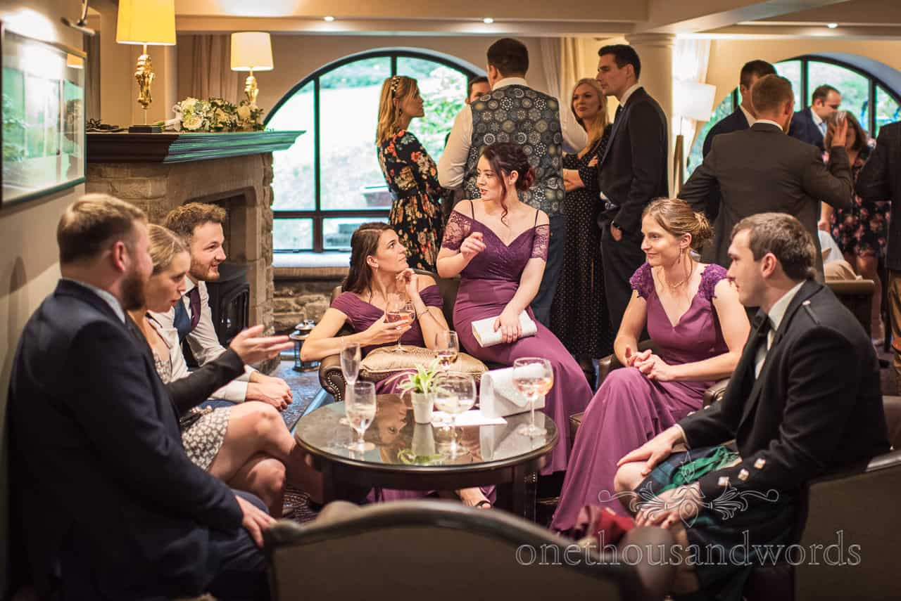 Documentary photograph of bridesmaids in purple dresses sitting with guests during drinks reception