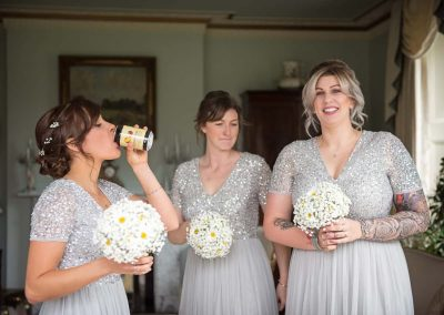 Bridesmaids in silver dresses drink cider cans with white daisy flower bouquets at Parley Manor wedding photograph