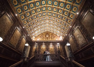 Canford School wedding photographers in Dorset capture bride and groom kissing on grand dark wooden staircase