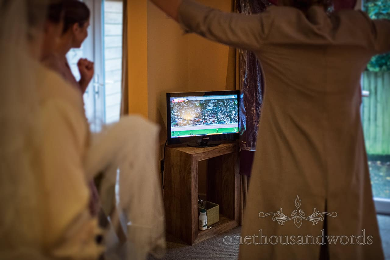 Bridal party celebrating England Rugby victory watched on TV during wedding morning preparation photographs