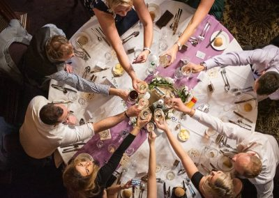 Circular wedding breakfast table guests make drinks toast from above photo by one thousand words wedding photographers
