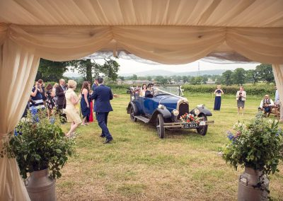 Classic wedding car arrives with bride at countryside marquee wedding in Dorset by one thousand words photographers