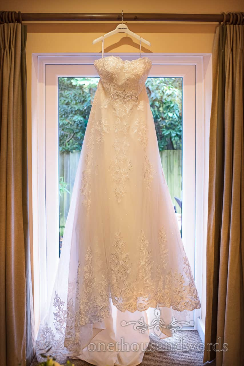 Classic white lace detailed wedding dress hangs between curtains in window on wedding morning