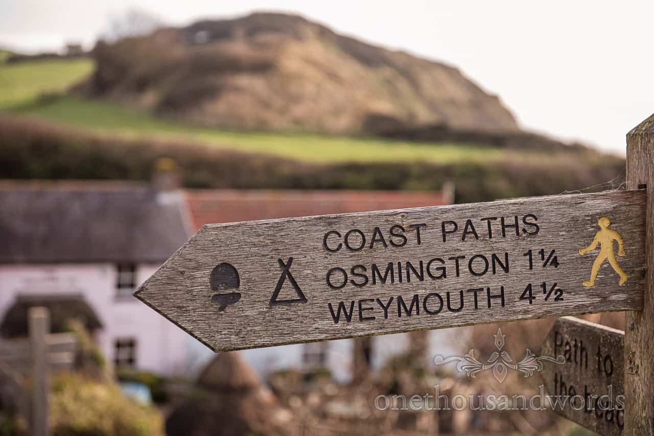 Photograph of Dorset coastal path wooden arrow footpath sign pointing to Osmington and Weymouth