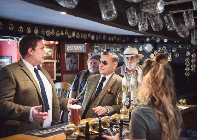 Groom in sunglasses leans on the bar in traditional English pub on wedding morning by Dorset documentary wedding photographers