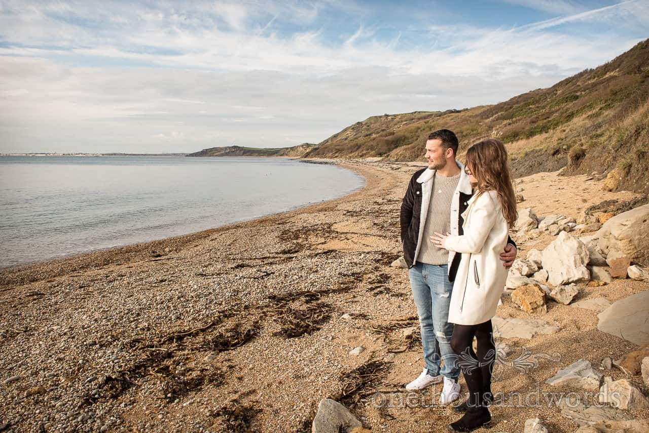 Loving couple look out to sea from Osmington beach at Dorset engagement photo shoot by one thousand words photography