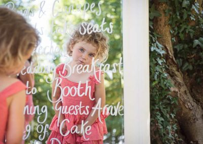 Cute child wedding guest natural photograph in reflection of wedding order of the day in white framed mirror