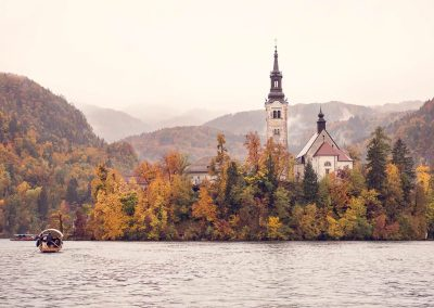 Destination wedding photo taken of boat at Lake Bled in Slovinia in Autumn by one thousand words wedding photographers
