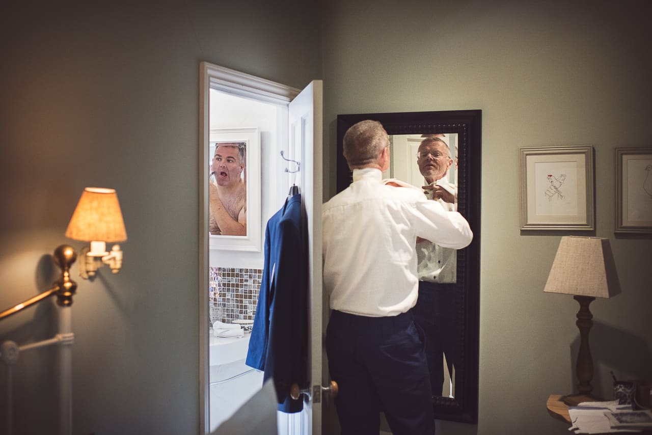 Documentary groom preparation photograph using mirrors shaving and putting wedding clothes on