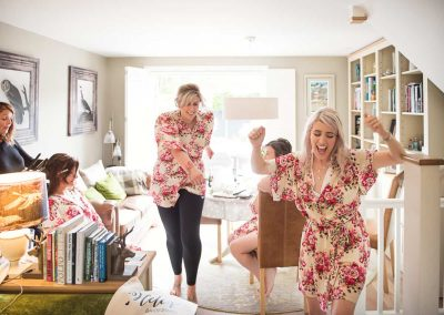 Documentary wedding photograph of bride and bridesmaids dancing in matching floral dressing gowns during bridal preparation