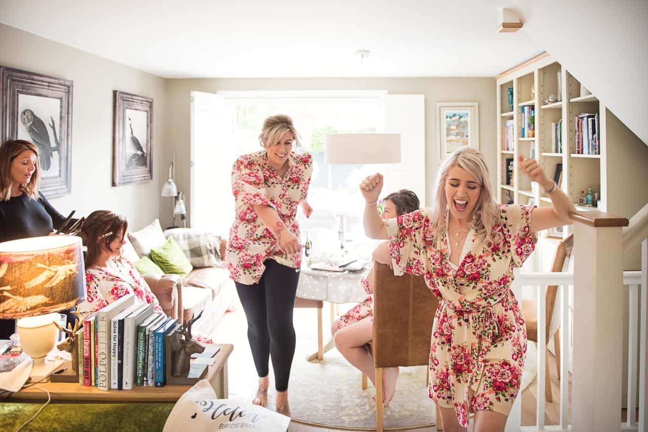 Bride and bridesmaids dancing to music in matching floral dressing gowns during bridal preparation