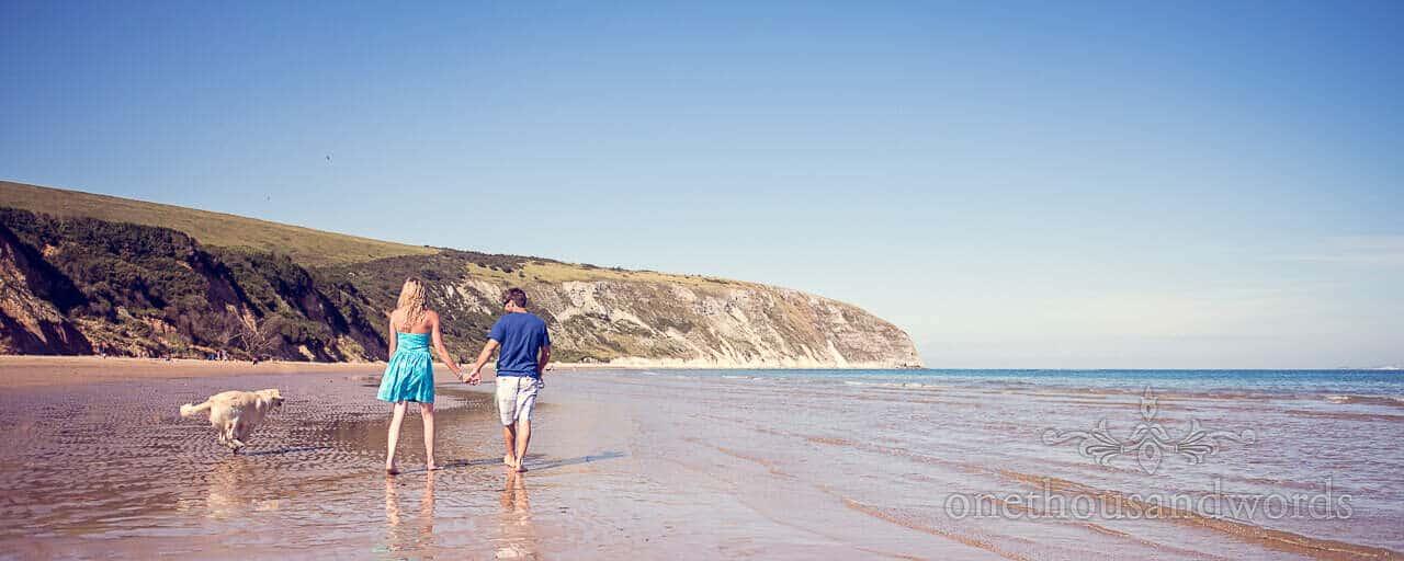 Top tips for engagement photos couple walk dog along beach as activity