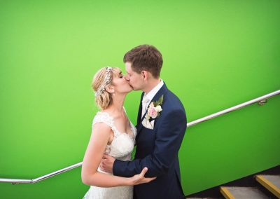 Dorset bride and groom kissing against green wall staircase in Swanage Dorset by one thousand words wedding photography