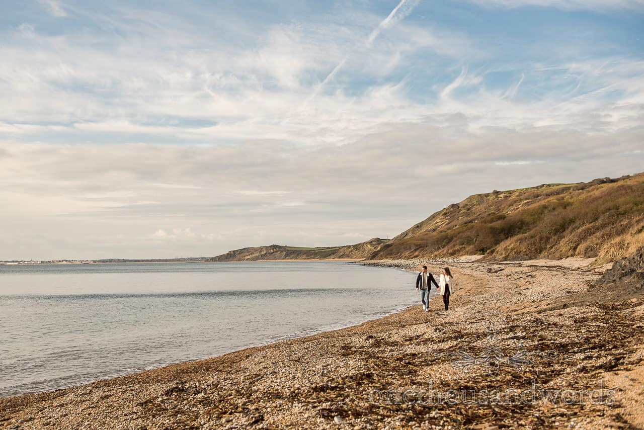 Dorset coastline photograph of engaged couple walking hand in hand along a beach by one thousand words photography