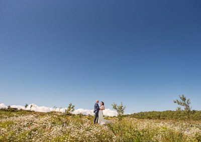 Dorset countryside wedding photograph of bride and groom in flower meadow with blue summer sky by one thousand words
