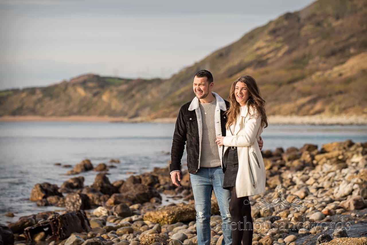 Dorset engagement photo shoot of couple laughing on stony Jurassic Coast beach by one thousand words wedding photography