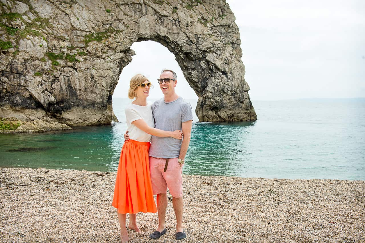 Engagement photo shoot couple on Durdledoor beach in Dorset with rock archway in sea