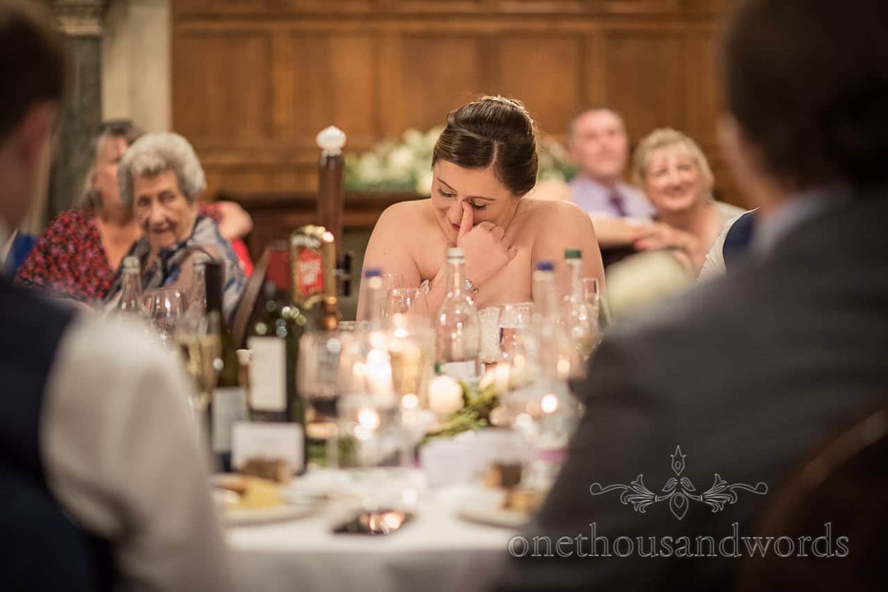 Emotional bride rubs tears away from her eyes during wedding breakfast documentary photographs by one thousand words photography