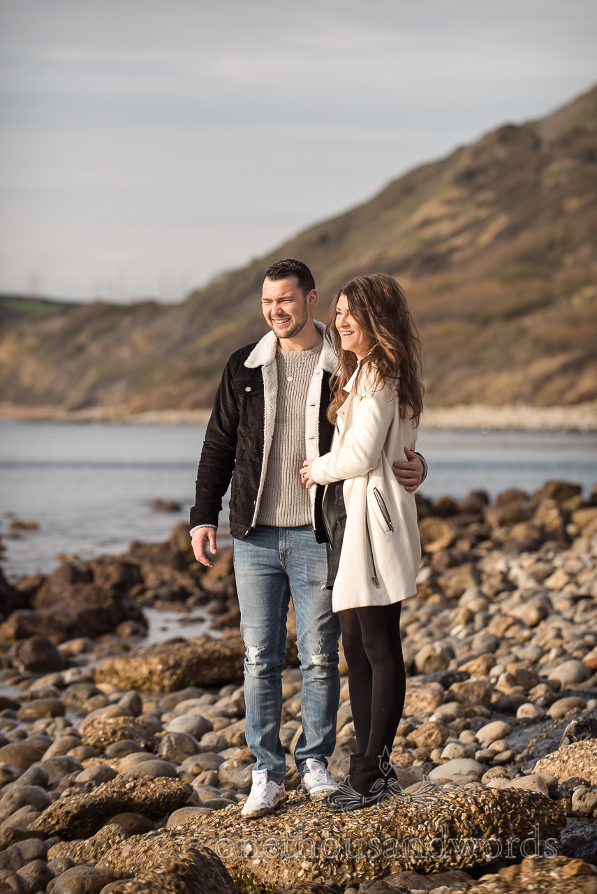 Engaged couple hug and laugh on rugged Dorset seaside beach photograph by one thousand words wedding photography
