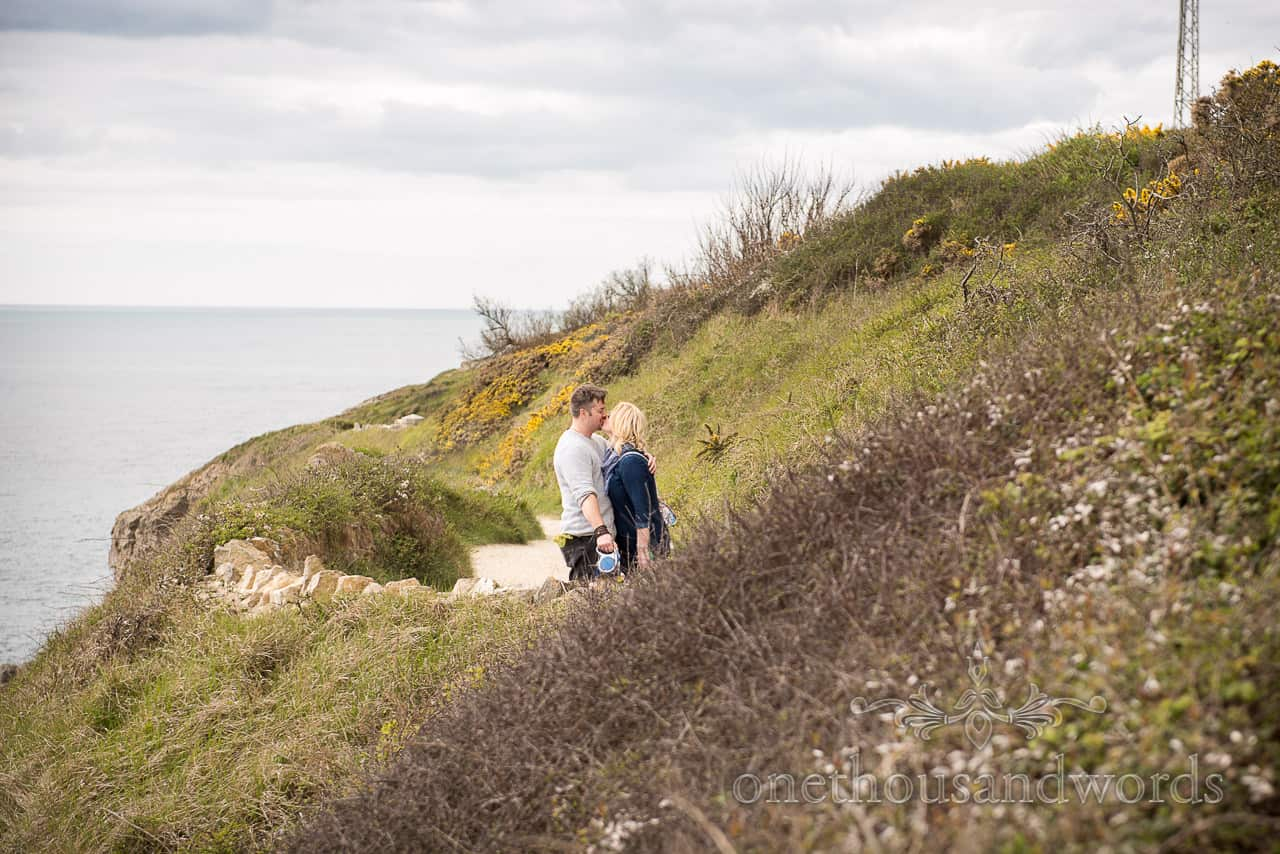 Engaged couple describe why you need an engagement shoot after photographs kissing on Dorset coastal footpath