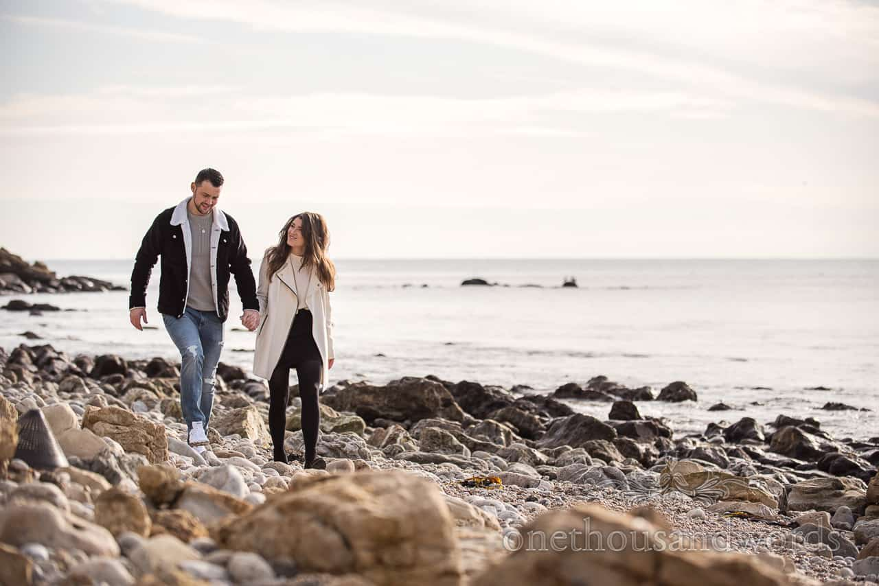 Engagement photograph of couple walking along stony Dorset beach captured by one thousand words documentary photography