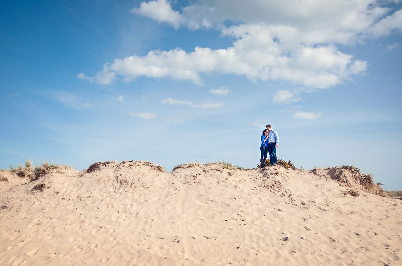 Example of engagement photo shoot image of couple standing on large sand dune without staged posing by one thousand words wedding photography