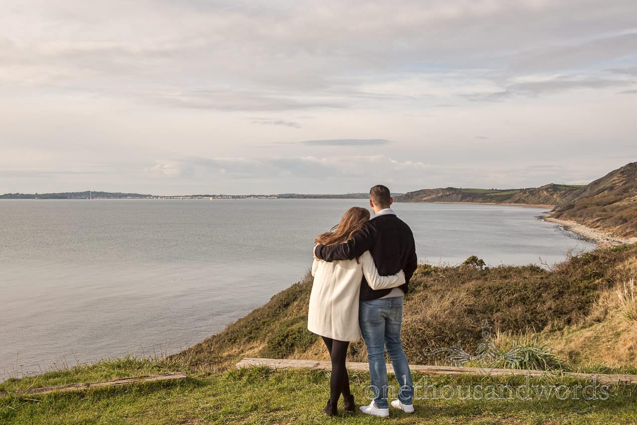 Engagement photograph of couple with Dorset coastal views at Osmington Mills by one thousand words wedding photographers