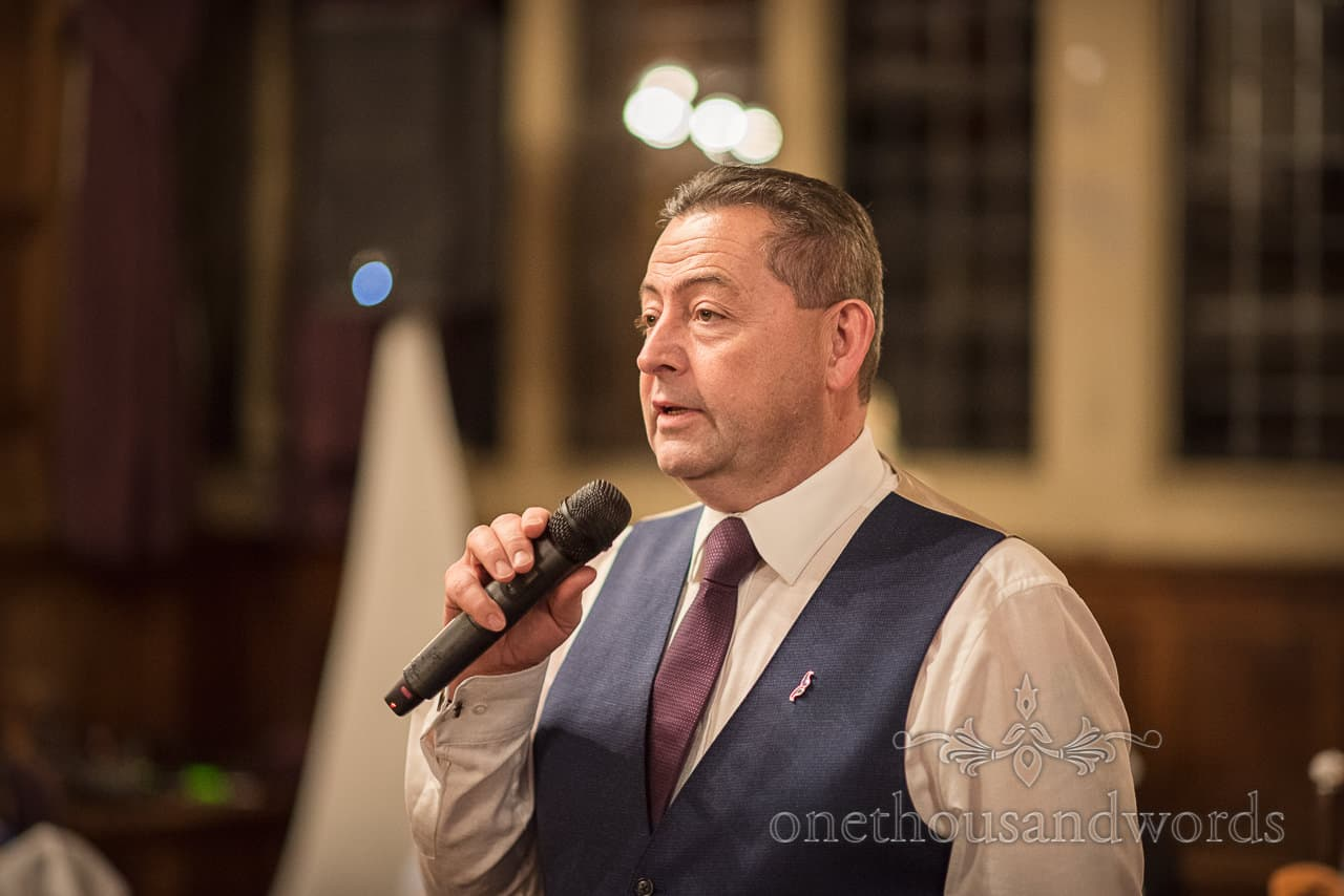 Portrait photograph of father of the bride in blue waistcoat delivering wedding speech using microphone
