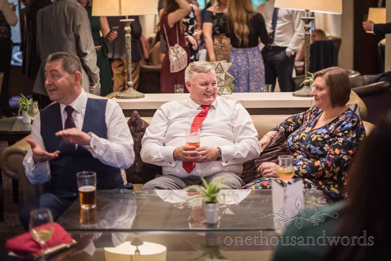 Wedding guest wearing red tie enjoys a beer at drinks reception in New Forest by one thousand words wedding photography