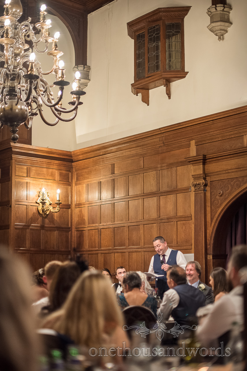Father of the bride makes wedding speech in wooden panelled grand hall with ornate candle lighting