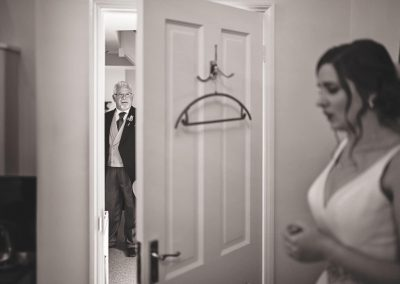 Father of the bride waits in doorway captured in black and white documentary wedding photograph by Dorset wedding photographers