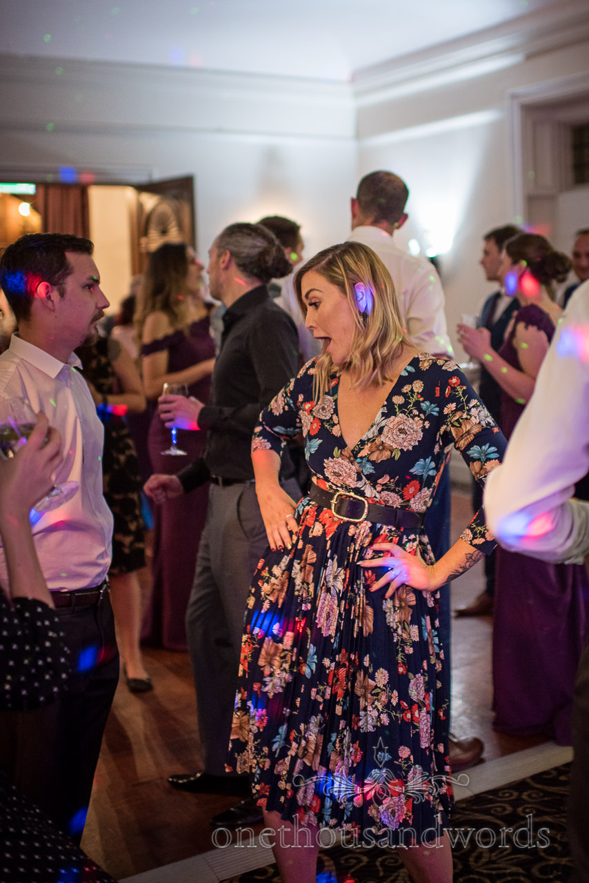 Female wedding guest in floral dress dances with hands on hips under disco lights on dance floor