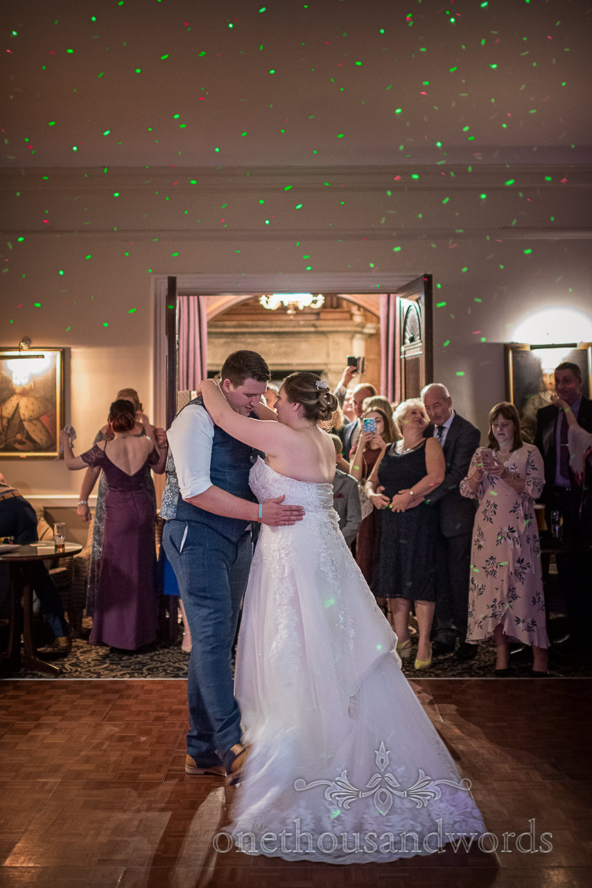 Bride and groom first dance lasers on Rhinefield House wooden dance floor photograph by one thousand words photography