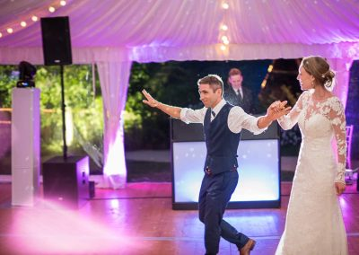 First dance back lit bride and groom in wedding marquee with disco lighting by documentary wedding photographers