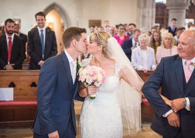 Fun wedding photograph father holding onto brides arm as she kisses groom in church wedding ceremony