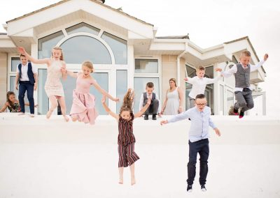Fun wedding photo at Sandbanks Hotel in Dorset of children jumping onto the beach by one thousand words photography
