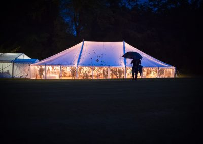 Glowing wedding marquee with wedding guest carrying umbrellas at Plush Manor wedding venue in Dorset by one thousand words