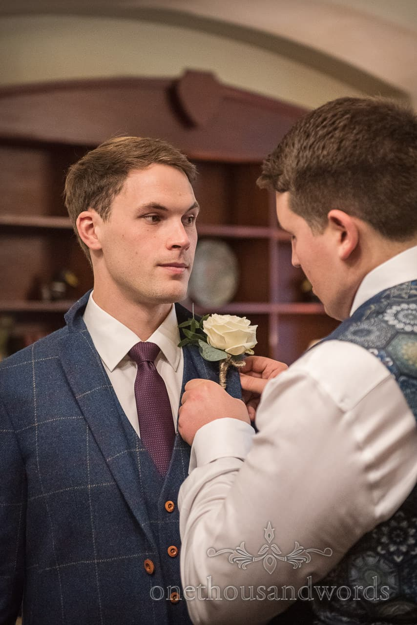 Documentary wedding photography of groom adjusting best man's floral buttonhole before the wedding ceremony