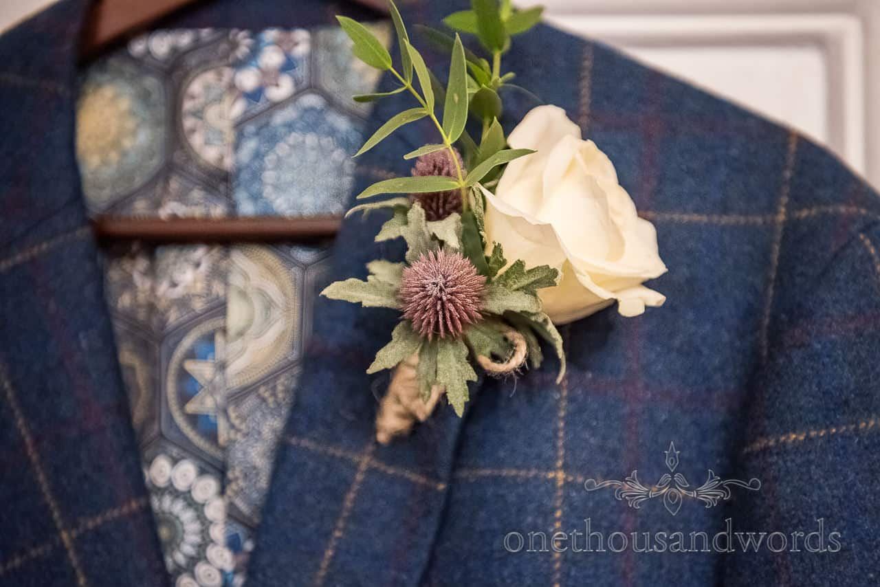 Grooms white rose buttonhole flower on blue tweed suit hanging on coat hanger by one thousand words wedding photography