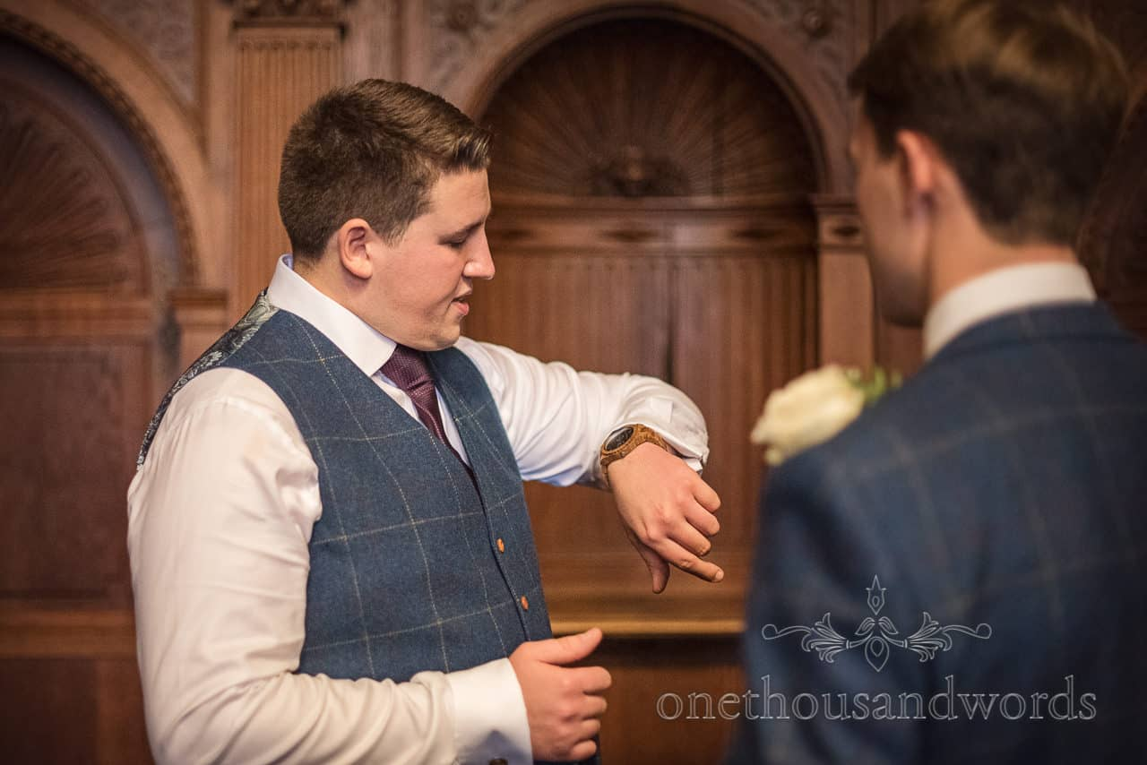Groom nervously checks his wooden watch before wedding ceremony in oak panelled room