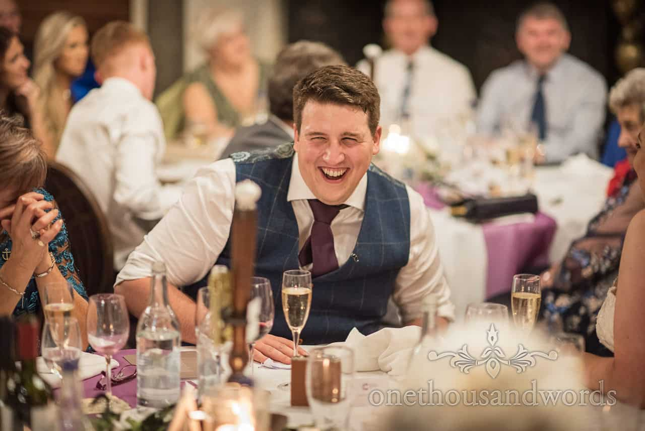 Documentary wedding photograph of groom in blue waistcoat laughing during wedding speeches at Rhinefield House Hotel